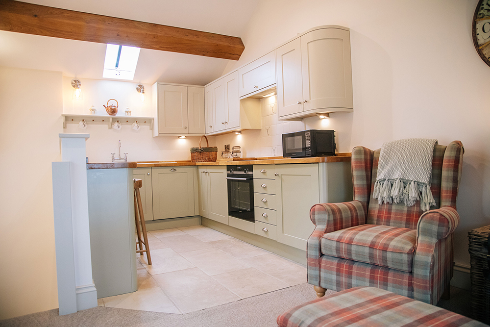 Kitchen and armchair in The Nook self-catering cottage